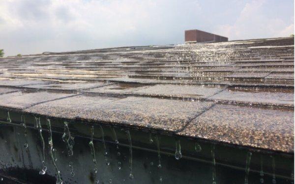 Asphalt roof house. Side view when it rains