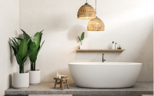 Interior of modern bathroom with white walls, concrete floor, white bathtub and shelf with creams and shampoo. Potted plants. 3d rendering