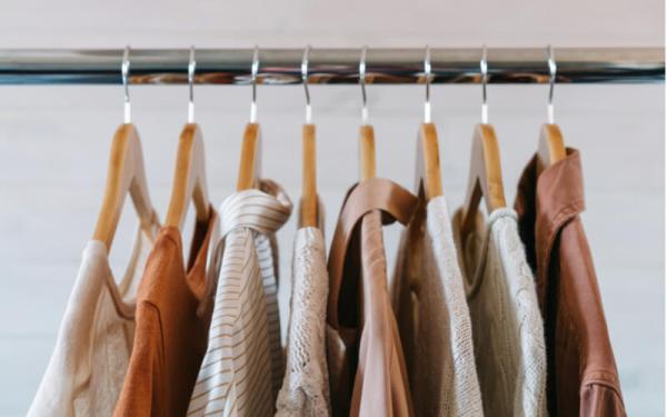 Close up cropped shot of the rack with warm pastel colored clothing collection on wooden hangers.