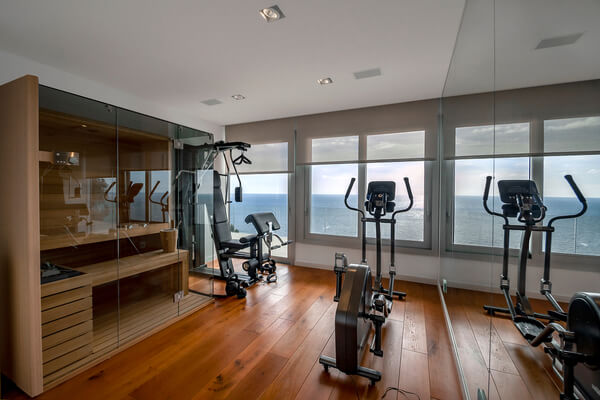 Sauna and fitness room with sea view. Traditional finnish sauna made from woodand glass door design in the sauna. Concept of: relax, vacation, wellness center.