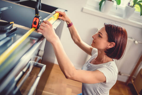 Woman working on a new kitchen installation and using leveling tool