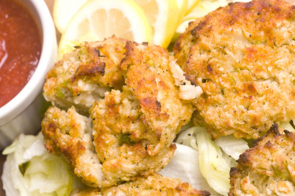 crab cakes with lemons and sauce in background
