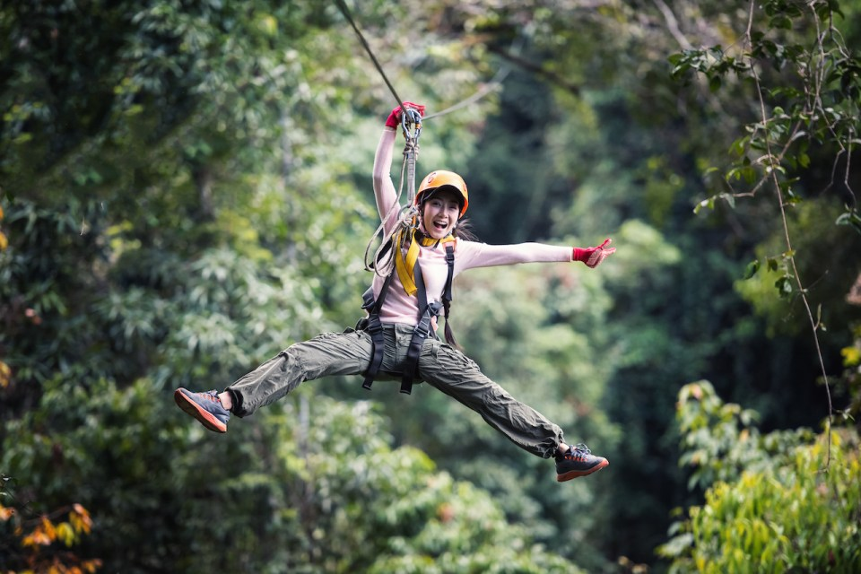 asian woman ziplining  with legs and arms out