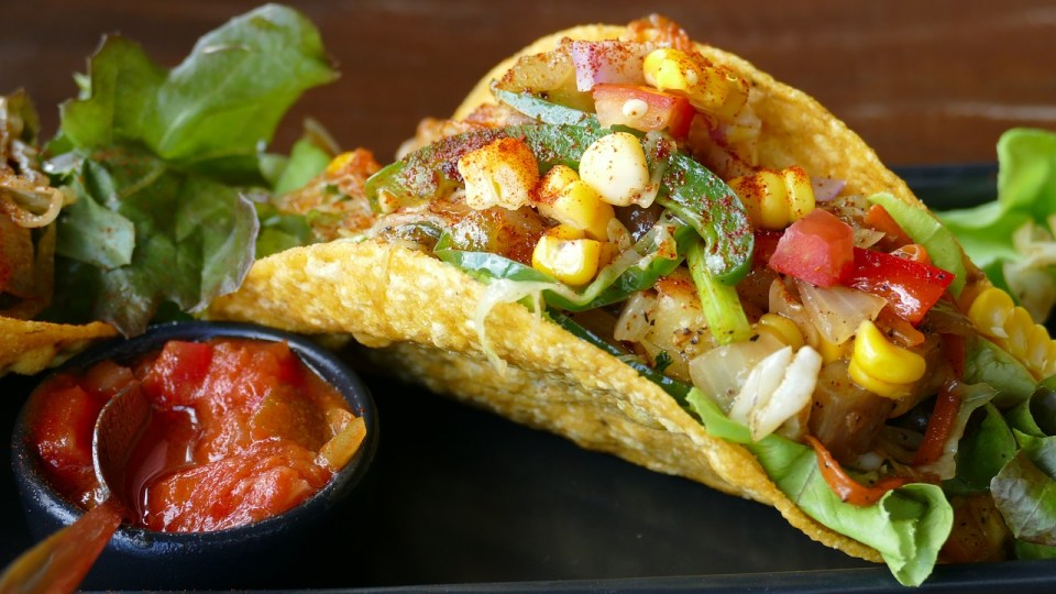 close up of a fresh hard shell taco with corn , tomatos and peppers inside with salsa on the side