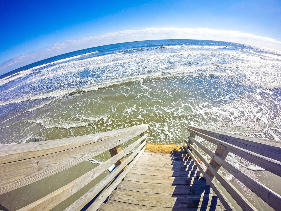 downward view of wooden steps stepping right out into the waves from Folly Beach, SC.