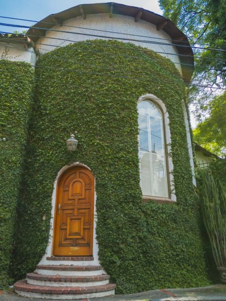 A short, rounded tower covered in ivy with an old wooden door.
