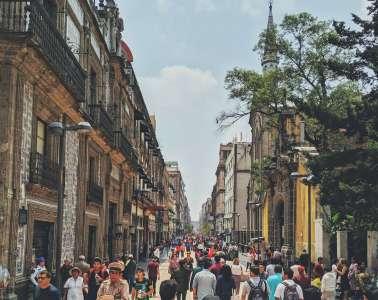 Historic buildings line a crowded street near the Iglesia del Convento de San Francisco in Mexico City.