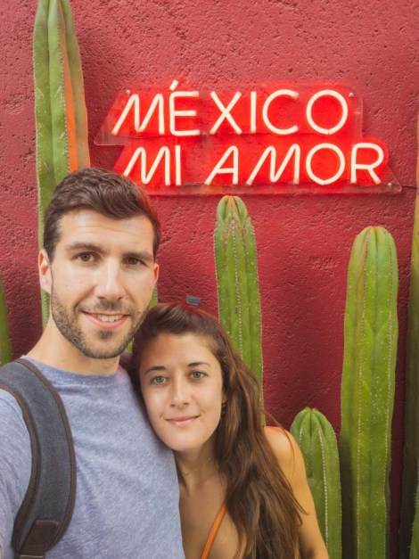 "A dark haired man poses with a long brown haired girl in front of a cactus and neon sign reading ""Mexico, Mi Amor""."