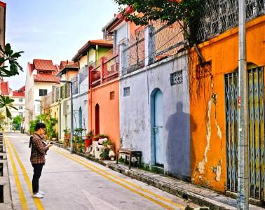 Man standing in alleyway with camera in front of colorful houses.