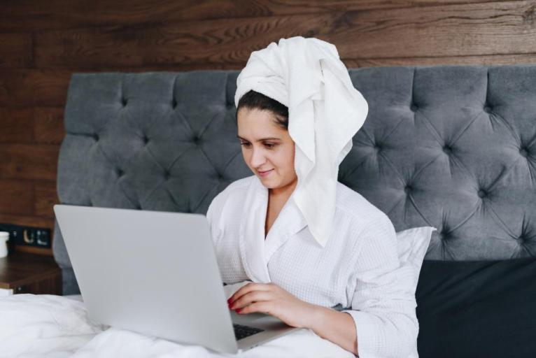 Woman works on laptop from hotel bed after shower.