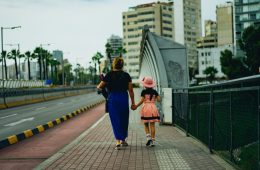 Mom and daughter hold hands as they take a walk on Mother's Day.