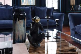 Black and gold monkey and vase on table
