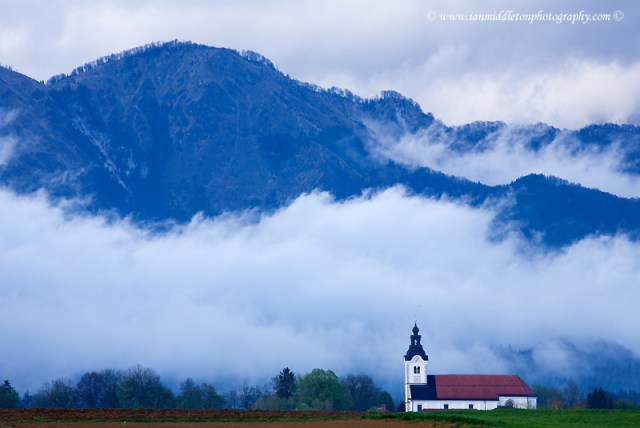 mountaintop of the Kamnik Alps appearing through the rain clouds after an evening storm with the church of Saint Peter sitting in its shadow. This complex also contains a castle, a baroque church, a parsonage, a cemetery and a fairly large stable.