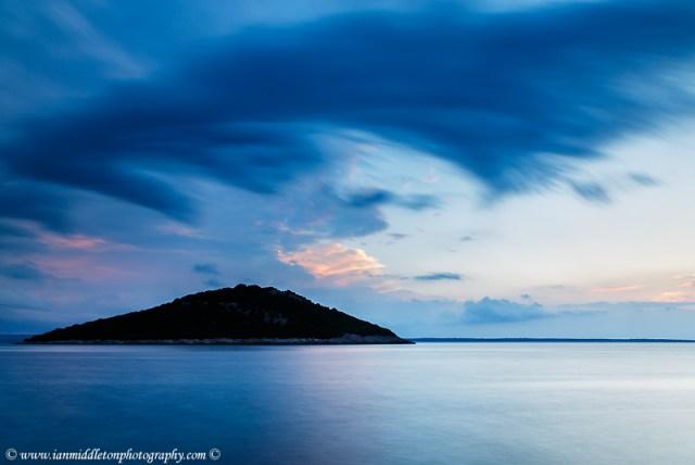 Storm moving in over Veli Osir Island at sunrise, seen from Zaosiri Beach, Cunski on Losinj Island, Croatia.