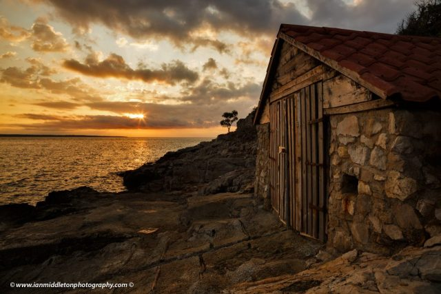 Sunrise over a boathouse on Zaosiri Beach on the coastal area of Cunski, which lies just 8kms north of Mali Losinj on Losinj Island, Croatia. The strip of land to the left is Punta Kriza.