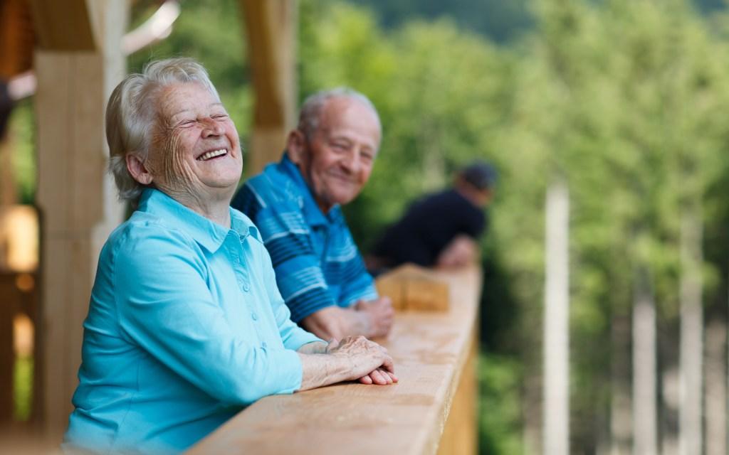 Casal de idosos sorrindo em um ambiente cercado de árvores.