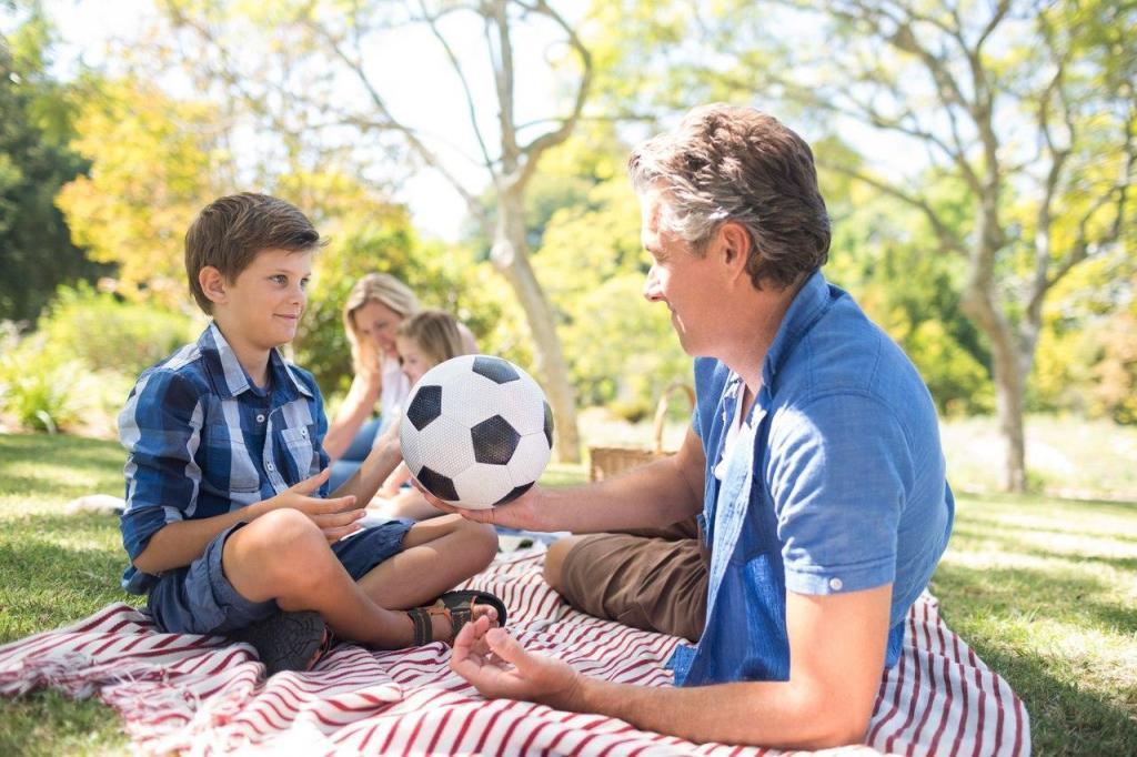 Avô e neto sentados, segurando uma bola de futebol