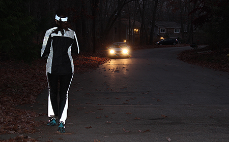 Woman running in reflective clothing with car in background