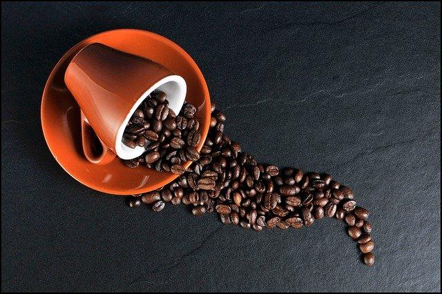 Xícara de café deitada sobre um pires com grãos de café saindo dela, como se estivessem sido espalhados.