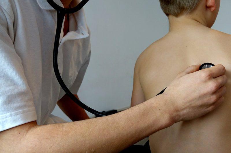 Médico auscultando os pulmões de uma criança com tosse seca.