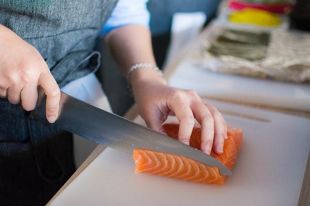 Pessoa cortando uma peça de salmão, alimento rico em ômega 3.