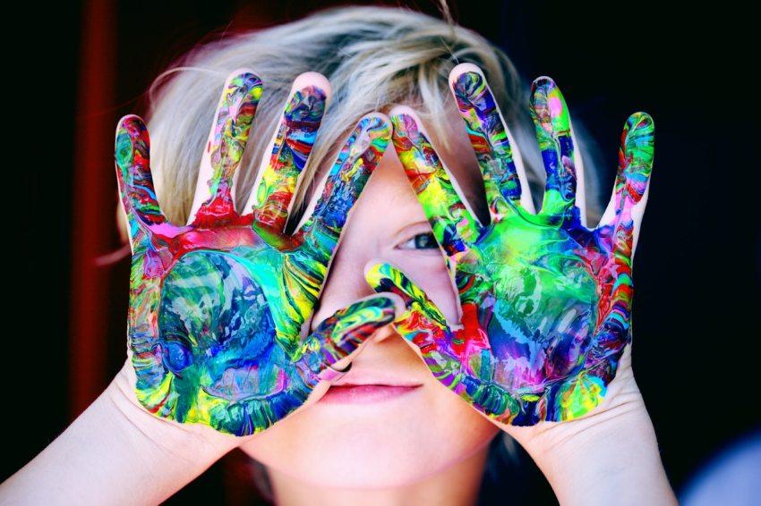 Criança com as mãos sujas de tinta na frente do rosto.