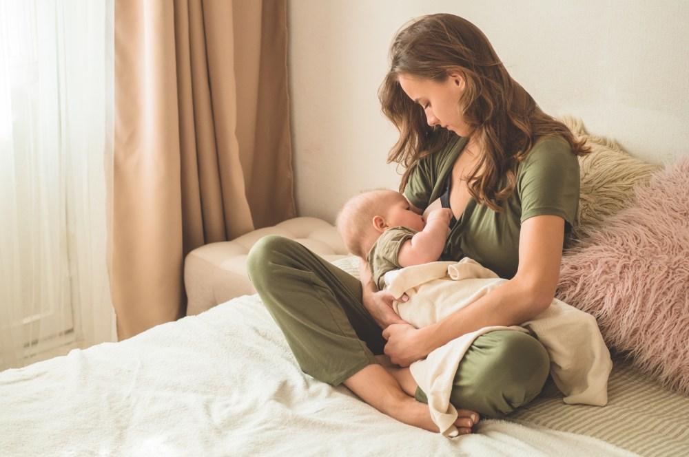 Uma mulher deitada na cama dando mama no peito para o bebê em seu colo.