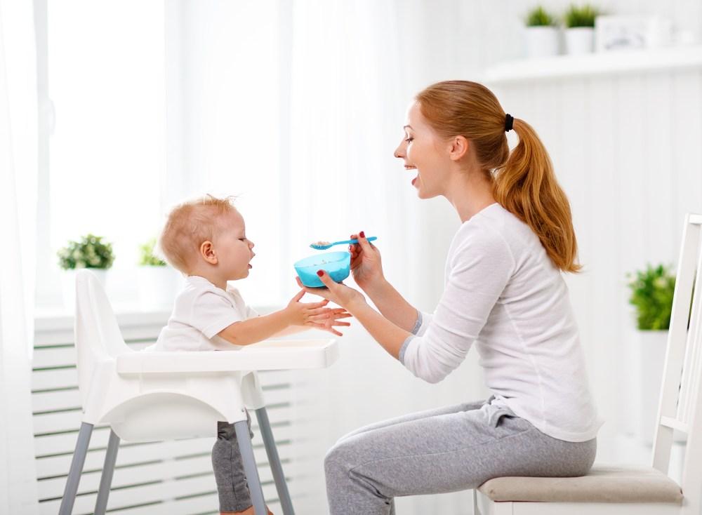 Uma mulher está sentada na frente de um bebê e oferece uma comida em uma colher para a criança.