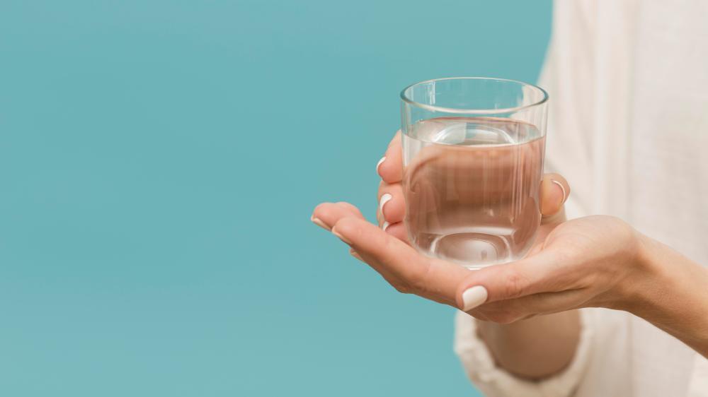Uma mão feminina segura um copo de água em um fundo azul.