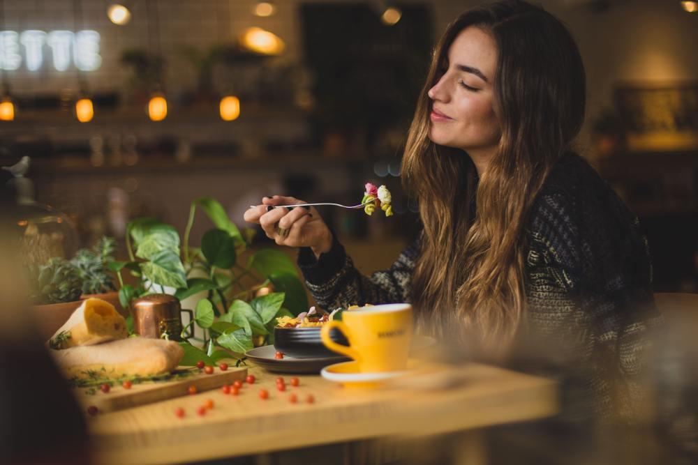 Uma mulher está sentada na mesa, segurando um garfo com um sorriso no rosto.