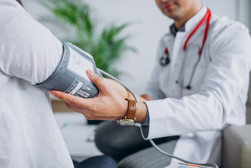 Jovem médico com paciente medindo a pressão arterial.