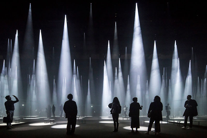 laurian-ghinitoiu at the forest of light. Cones of light stream down from the black ceiling like many spotlights on the ground
