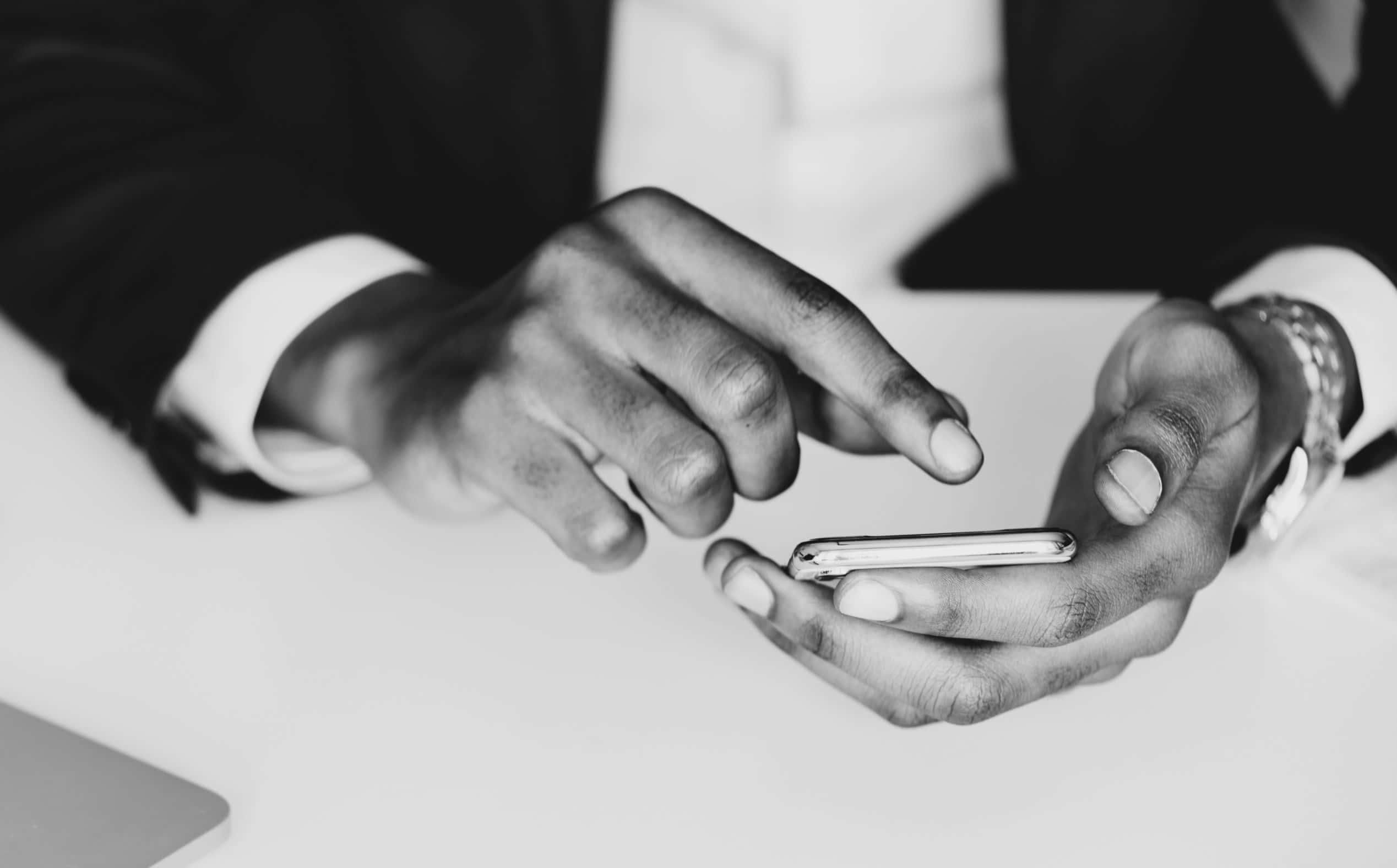 Foto detalhada e focada em um par de mãos mexendo em um celular, ilustrando o texto