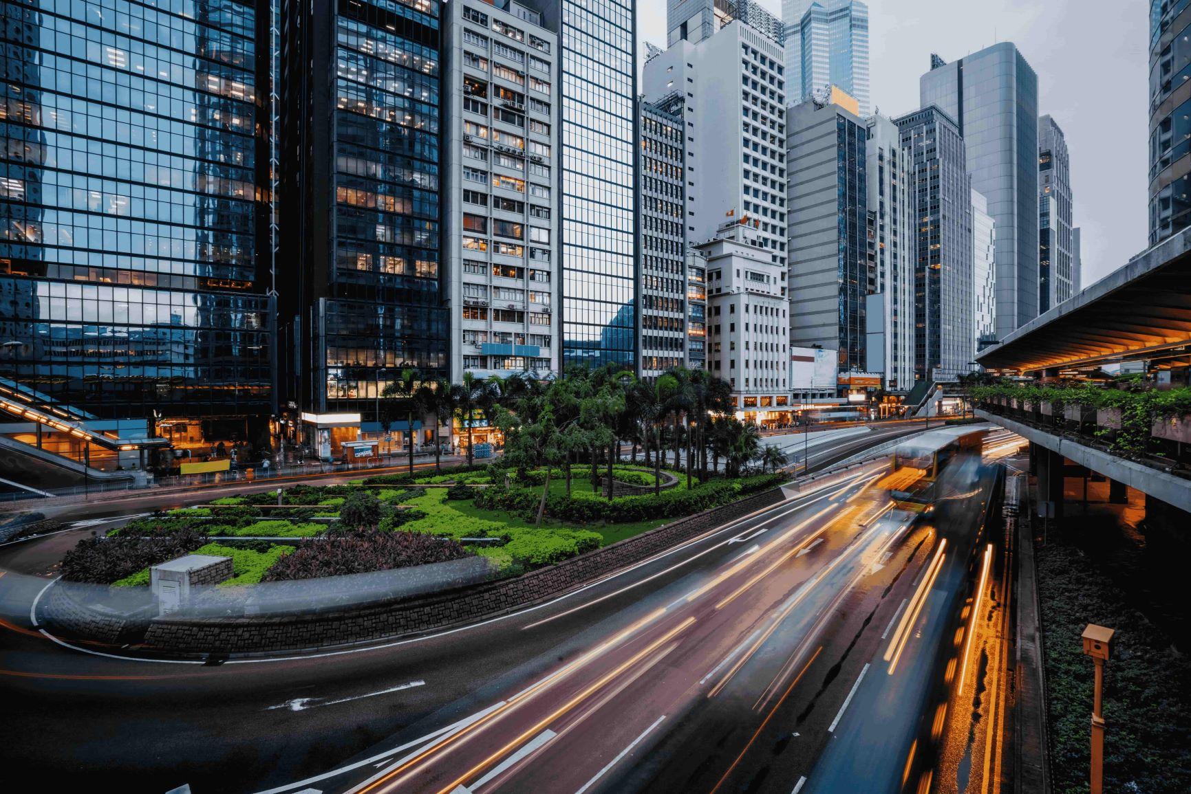 Foto no formato paisagem de uma cidade com uma rodovia em movimento. A foto ilustra uma cidade digital, cercada por áreas verdes e prédios.