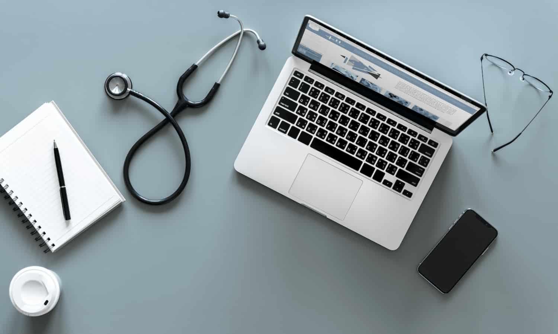 foto com vista aérea de um notebook, ao lado de um estetoscópio, um smartphone e um bloco de notas. A imagem visa ilustrar o conteúdo sobre