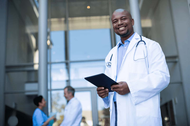 Foto de um médio em frente a um hospital, segurando um tablet, ilustrando saúde e tecnologia.