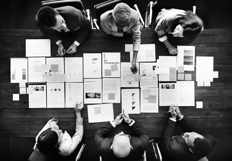 Pessoas sentadas em uma mesa de reunião, analisando estatísticas.
