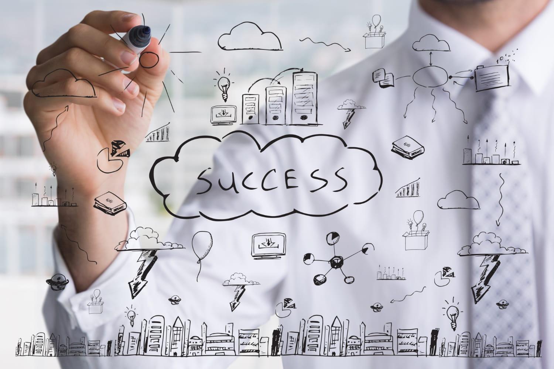 Homem de negócios desenhando em uma lousa ospassos para o sucesso.