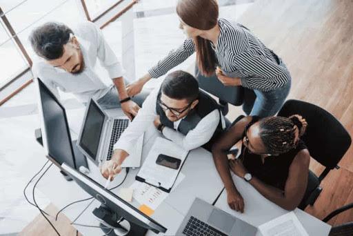 Pessoas reunidas em frente a uma mesa de escritório e olhando para a tela de um laptop