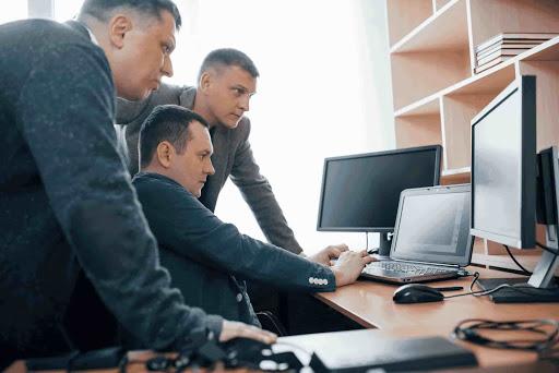 3 homens de paletó em uma sala de reunião, observando a tela de um computador