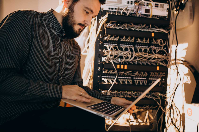 Imagem um homem, profissional de ti, analisando servidores.