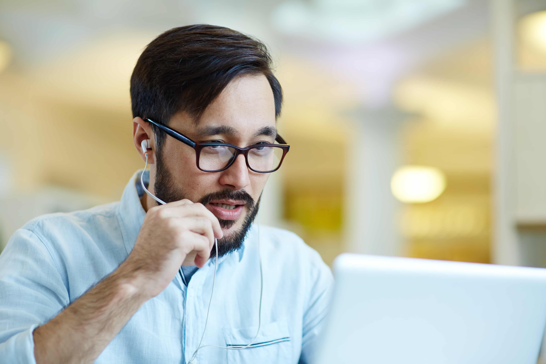 Homem olhando para tela de notebook, participando de conversa por videoconferência.