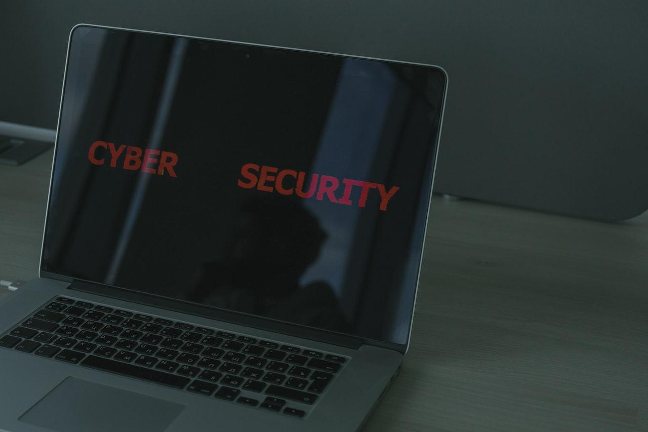 """Notebook aberto sobre plataforma de madeira. Na tela do notebook está escrito """"Cyber Security"""""""