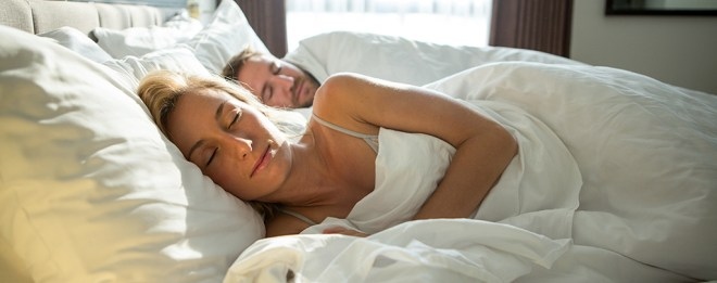 Cheerful young couple sleeping in a comfortable bed in an hotel room in the morning. The sunlight is coming in the room.