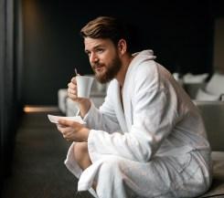 Man in bathrobe drinking coffee