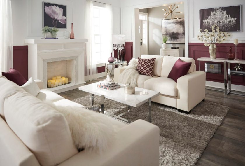 Glam designed living room with white couch, purple pillows and marble tables