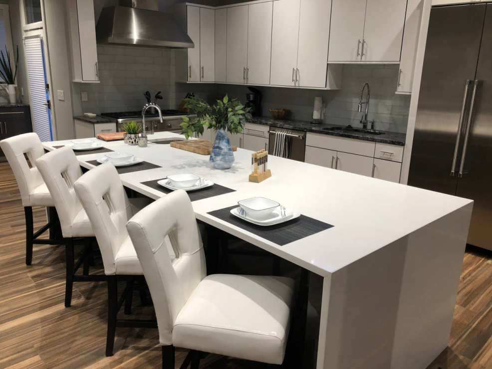 iNSPIRE Q white faux leather upholstered bar stools with key hole back in kitchen of North Carolina Airbnb