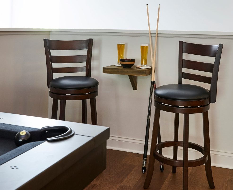 Tying into one of our previous man cave ideas, seats at the bar helps keep your space clean and while your drinks are still within reach. These bar stools have a warm cherry finish and rich, black leather upholstery on round seats. They also come with rounded footrests, high backrests, and a swivel feature so nothing is sacrificed when it comes to snacks.