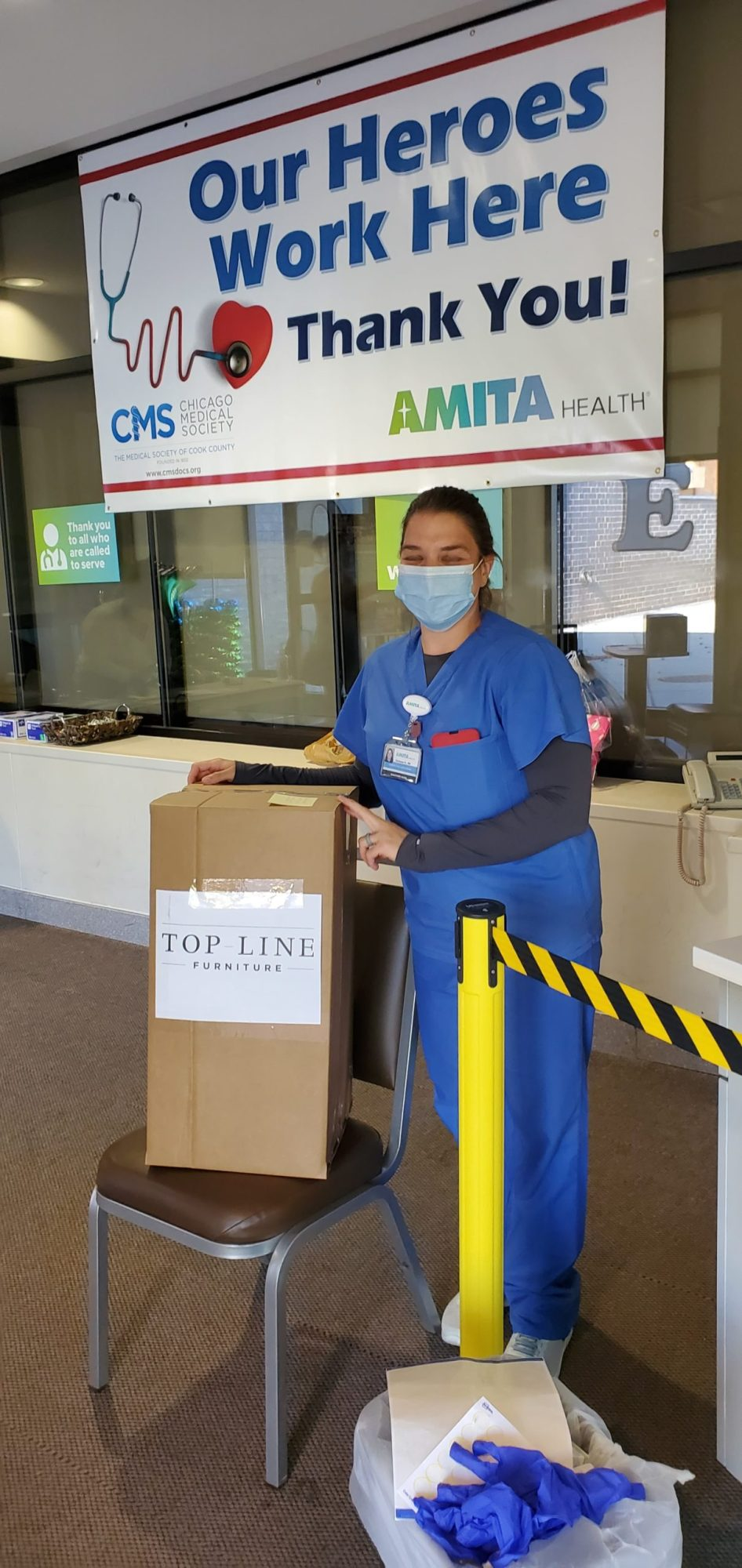 A healthcare worker from AMITA Health with a packaged face shield donation from Inspire Q.