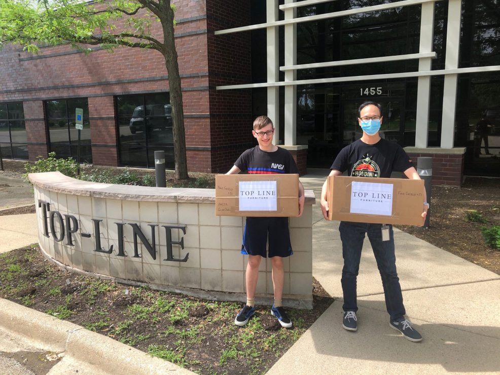 Inspire Q team member Allen Yau stands with a volunteer from GetUsPPE.org. Both are holding packages of face shields for essential workers.